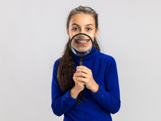 コピースペースで白い壁に隔離された歯を示す口の前に虫眼鏡を保持している遊び心のある10代の少女