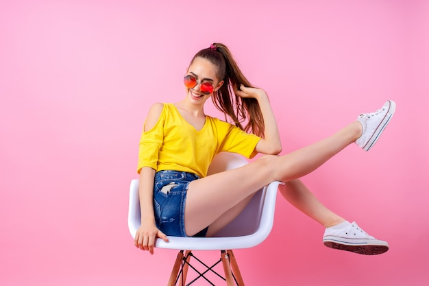 Playful teenage girl sitting in chair with legs raised
