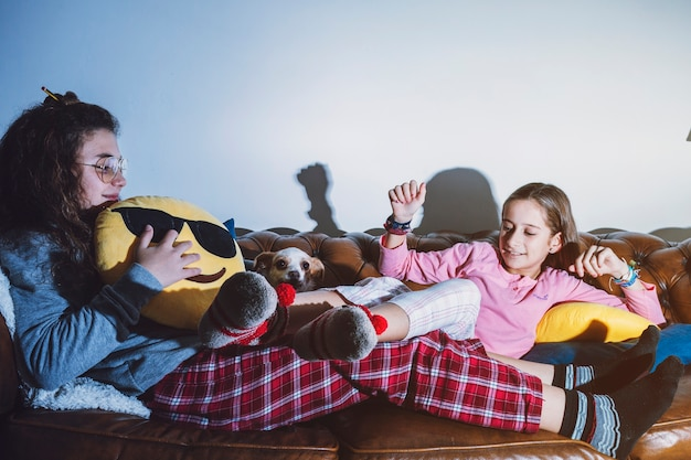 Playful teens with dog on couch