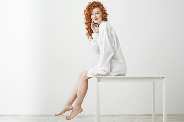 Игривая нежная женщина с вьющимися рыжими волосами, смеясь, позирует, сидя на столе. копировать пространство