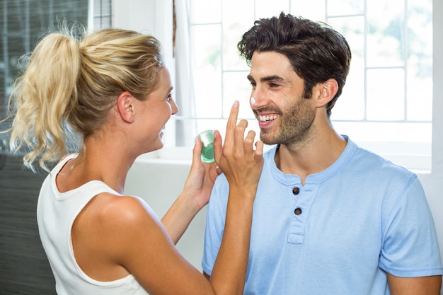 Playful woman applying cream on man's nose