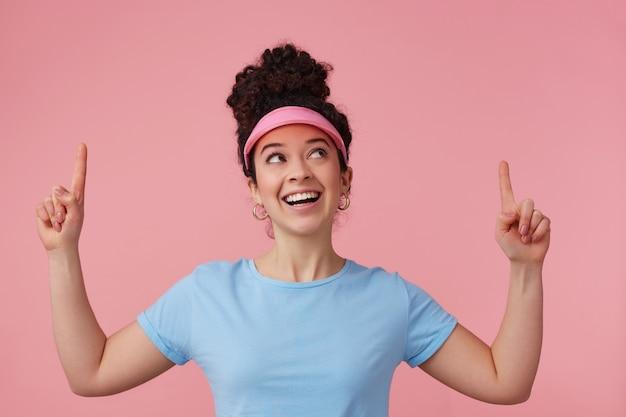 遊び心のある女性、暗い巻き毛のお団子を持つ美しい少女。ピンクのバイザー、イヤリング、青いtシャツを着ています。補う