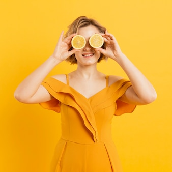 Playful woman covering eyes with lemon slices