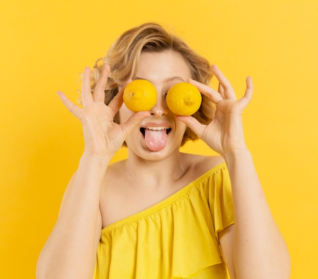 Playful woman covering eyes with lemons