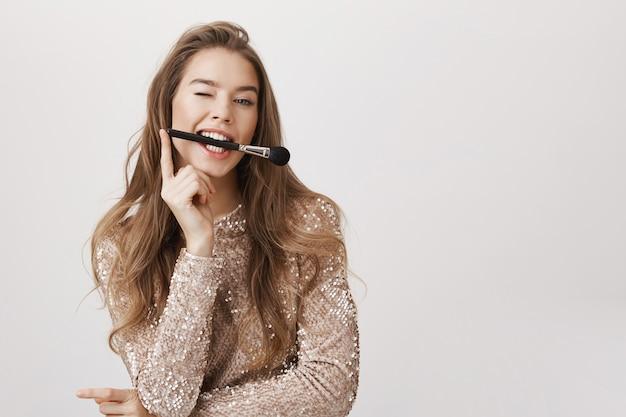 Игривая женщина держит щетку в зубах, выглядит нахально