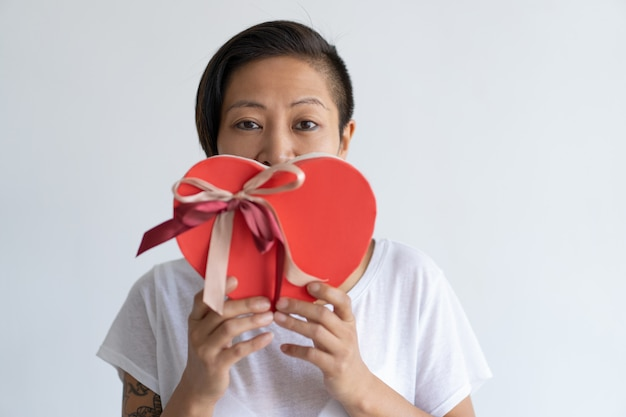 Playful woman holding heart shaped gift box in front of mouth