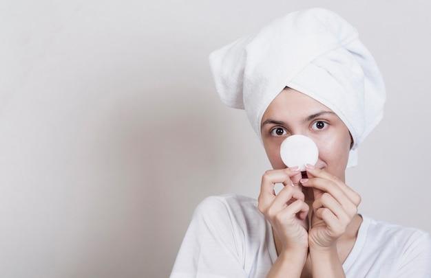 Playful woman holding makeup disc