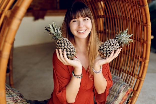 Игривая женщина держит два ананаса, сидя на бамбуковом стуле