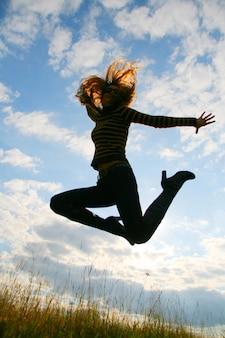 푸른 흐린 하늘에서 점프 장난 여자