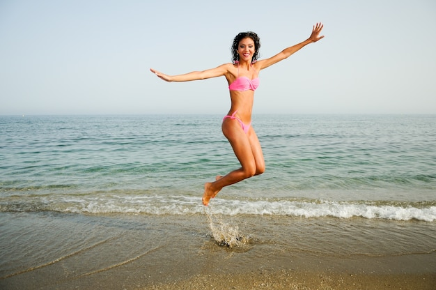 Playful woman jumping on the shore