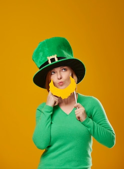 Playful woman in leprechaun costume looking at copy space