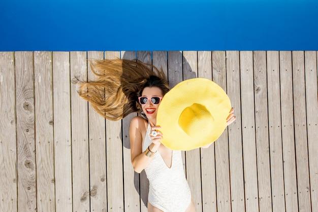 Игривая женщина, лежащая в желтой шляпе от солнца у бассейна. концепция летних каникул