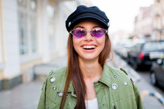 Игривая женщина позирует на улице. ношение модных фиолетовых ретро-очков, черная кепка