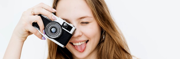 Playful woman taking a picture with a film camera