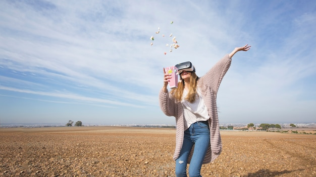 Playful woman in vr goggles throwing popcorn