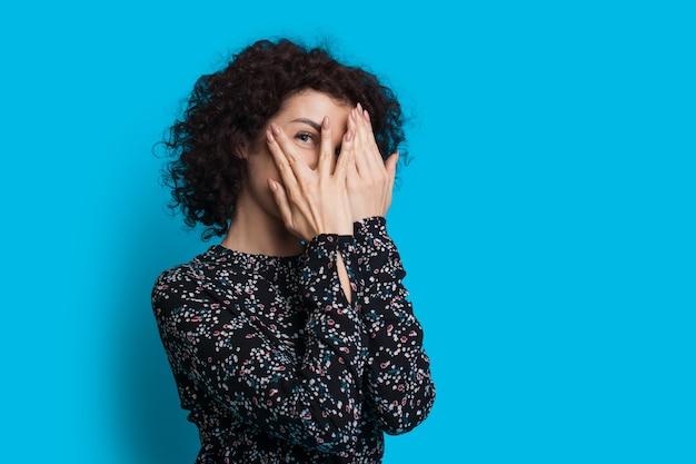 Игривая женщина с вьющимися волосами прячется от камеры, прикрываясь ладонями