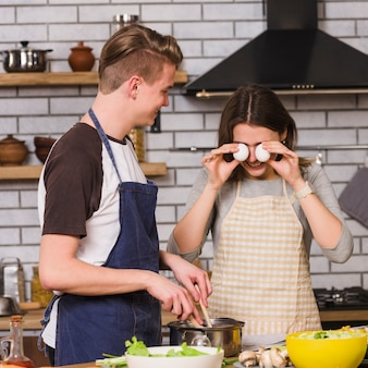 Playful woman with man cooking in kitchen