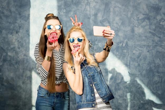 Игривые женщины веселятся со сладкими пончиками на синем фоне стены