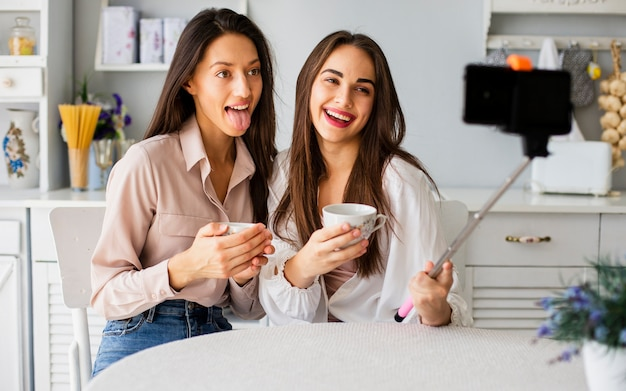 Playful women at home taking selfies