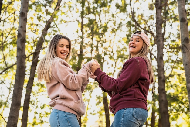 Playful women looking at camera holding hands