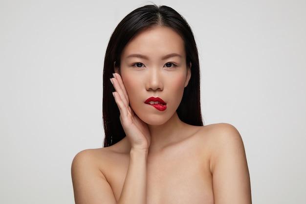 裸の肩で白い壁の上に立って、コケティッシュに彼女の下唇を噛みながら彼女の頬に上げられた手のひらを保持している遊び心のある若い美しい黒髪の女性