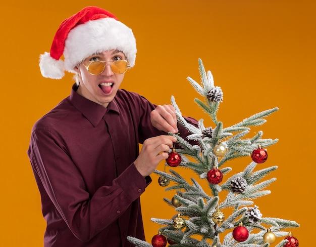 Giocoso giovane uomo biondo che indossa il cappello della santa e occhiali in piedi in vista di profilo vicino all'albero di natale decorarlo con palline di natale guardando la telecamera che mostra la lingua isolata su sfondo arancione
