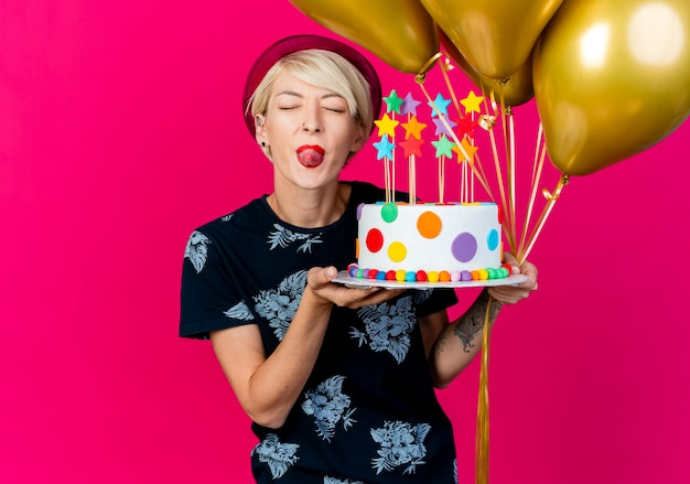 Playful young blonde party girl wearing party hat holding balloons and birthday cake with stars showing tongue with closed eyes isolated on crimson background with copy space