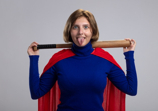 Playful young blonde superhero girl in red cape holding baseball bat behind neck looking at camera showing tongue isolated on white background
