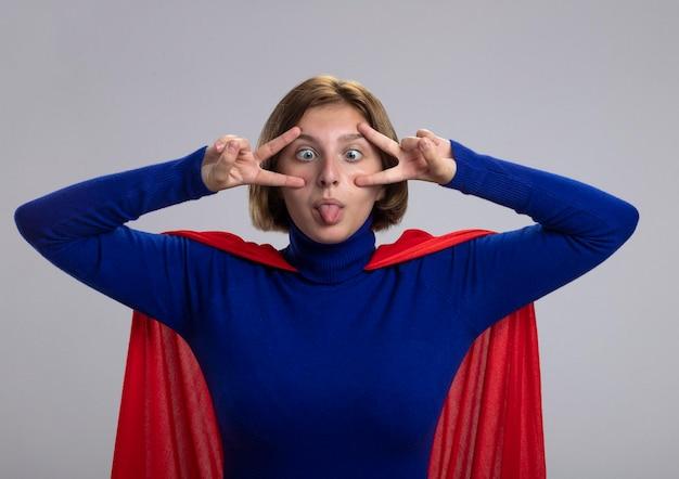 Giocosa giovane donna bionda del supereroe in mantello rosso che fa segno di pace che mostra la lingua che attraversa gli occhi isolati sulla parete bianca