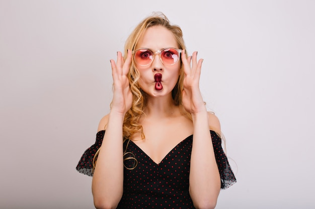 Playful young blonde  with red lips making fish face, young woman having fun, being crazy. wearing pink stylish glasses, black dress, has long curly hair.