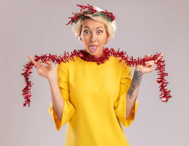 Игривая молодая блондинка в рождественском головном венке и гирлянде из мишуры на шее, глядя в камеру, хватая гирлянду из мишуры, показывая язык, изолированные на белом фоне