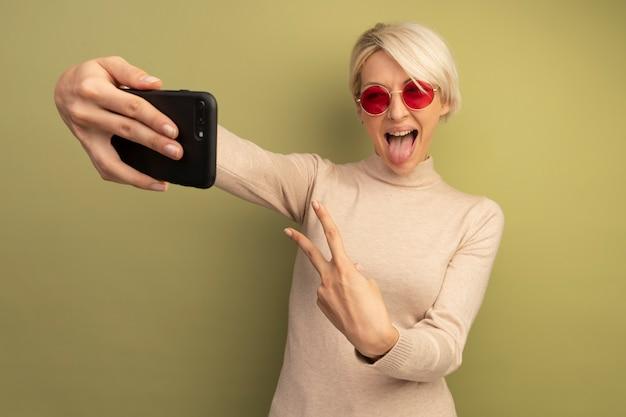 올리브 녹색 벽에 고립 된 셀카를 찍는 혀를 보여주는 평화 기호를 하 고 선글라스를 착용 장난 젊은 금발의 여자