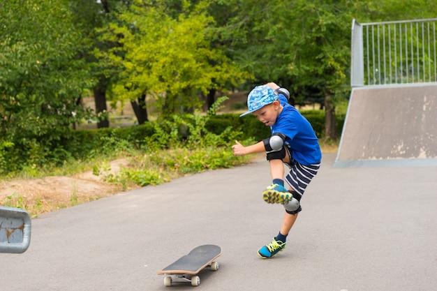 スケートパークで日差しの中で遊んでいる間、彼のスケートボードを繁栄で蹴っている遊び心のある少年
