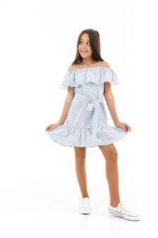 Игривая молодая брюнетка девушка в платье позирует и смотрит в сторону на белом