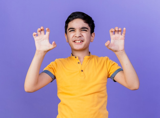 Giovane ragazzo caucasico allegro che fa il ruggito della tigre e il gesto delle zampe isolato sulla parete viola