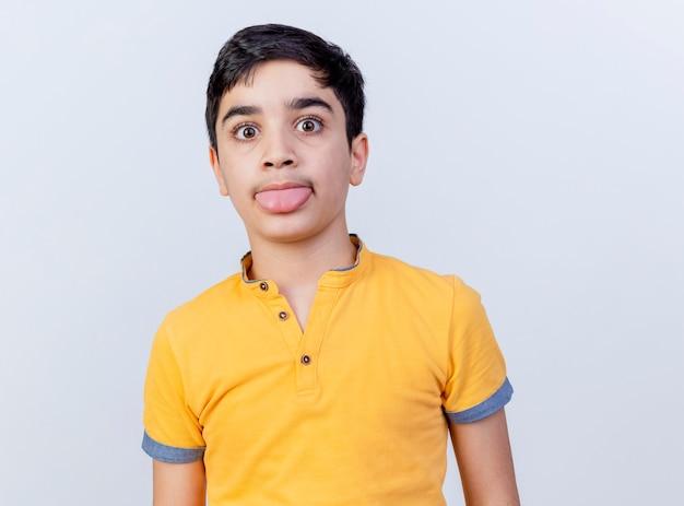 白い背景で隔離の舌を示すカメラを見て遊び心のある若い白人少年