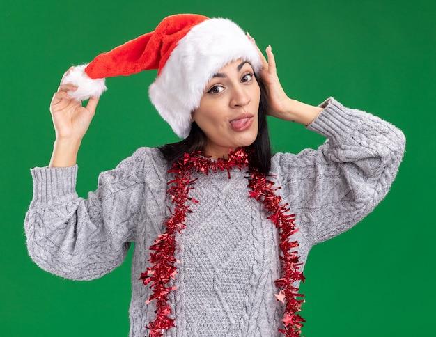 クリスマスの帽子と見掛け倒しのガーランドを身に着けている遊び心のある若い白人の女の子は、緑の背景に分離された舌を示すカメラを見て頭に触れて帽子をつかむ