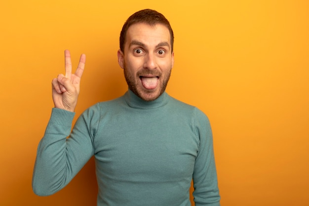 Giocoso giovane uomo caucasico che mostra la lingua facendo segno di pace isolato sulla parete arancione con copia spazio