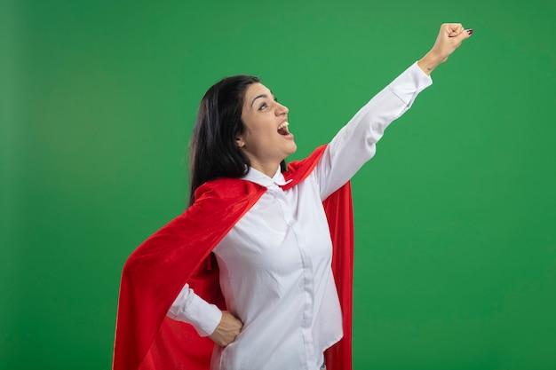 Игривая молодая кавказская девушка-супергерой, стоящая в профиль в позе супермена, поднимает кулак и смотрит в угол, держа руку на талии, изолированной на зеленом фоне с копией пространства