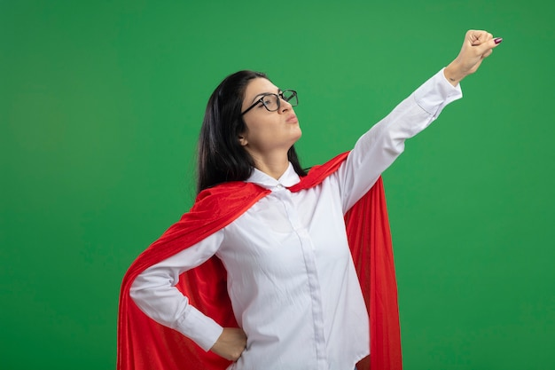Игривая молодая кавказская девушка супергероя в очках, стоящая в позе супермена в профиль, поднимает кулак на зеленом фоне с копией пространства