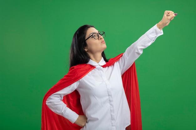 Giocoso giovane supereroe caucasico ragazza con gli occhiali in piedi in superman posa in vista di profilo alzando il pugno isolato su sfondo verde con spazio di copia