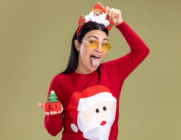 Playful young caucasian woman wearing santa headband and sweater with glasses holding christmas tree toy