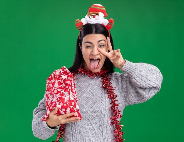 Playful young caucasian woman wearing santa headband and tinsel garland around neck holding christmas gift