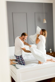 Playful young couple having pillow fight on bed