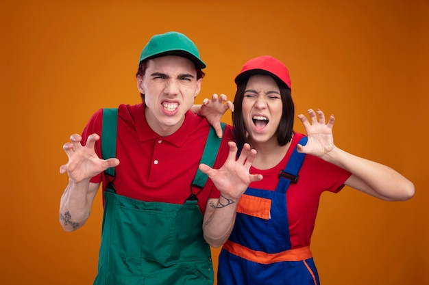 オレンジ色の壁に隔離された目を閉じてカメラの女の子を見て虎の足のジェスチャーの男をやっている建設労働者の制服と帽子の遊び心のある若いカップル