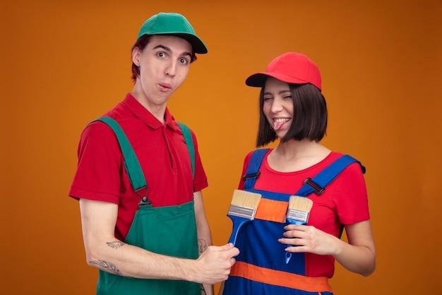 건설 노동자 유니폼과 모자 여자 가슴 앞에 페인트 붓을 들고 장난 젊은 부부는 고립 된 닫힌 된 눈으로 혀를 보여주는 놀란 남자 바보 소녀