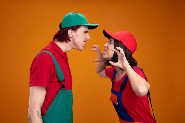 オレンジ色の壁に分離された虎の足のジェスチャーをしている歯の女の子を示しているお互いの男を見ている建設労働者の制服と帽子の遊び心のある若いカップル