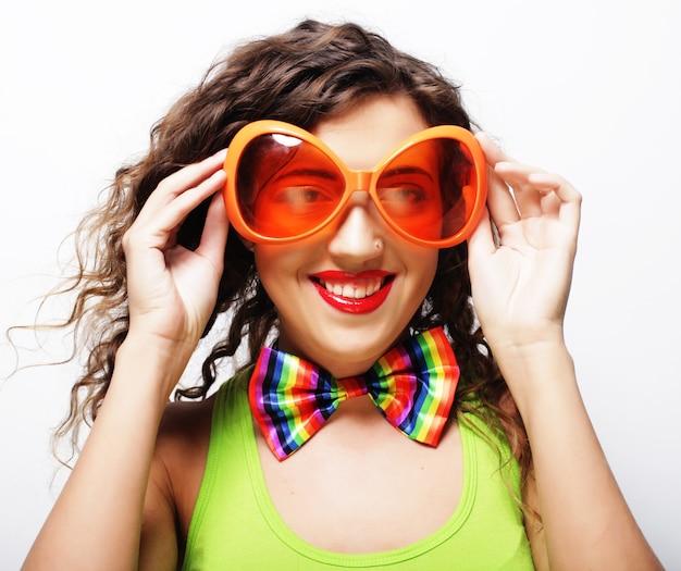 パーティーグラスを持つ遊び心のある若い巻き毛の女性。
