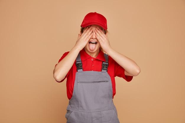 Giocosa giovane operaio edile femminile che indossa l'uniforme e cappuccio che copre gli occhi con le mani che mostrano la lingua