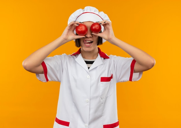 Giocoso giovane cuoco femminile in uniforme da chef mettendo i pomodori sugli occhi e mostrando la lingua isolata su sfondo arancione
